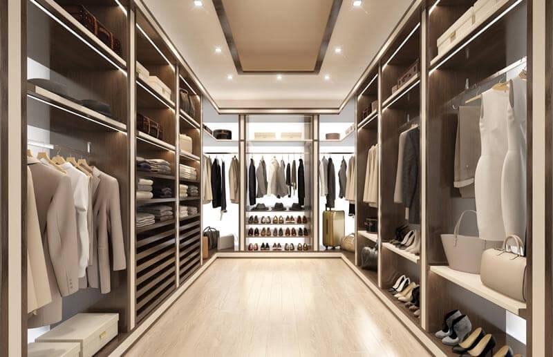 Begehbare Ankleide in hellen Farben im Seitensystem mit mehreren Tablaren und Kleiderstangen. Dazu edle Schubladen in Besch- und braunem Design. Im Hintergrund befinden sich beleuchtete Acrylgläser.