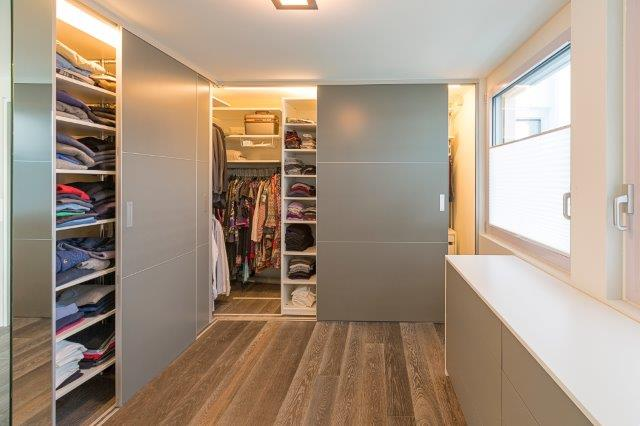 Ein begehbarer Kleiderschrank über Eck mit grauen Schiebetüren und einer integrierten Beleuchtung mit automatischer Einschaltfunktion