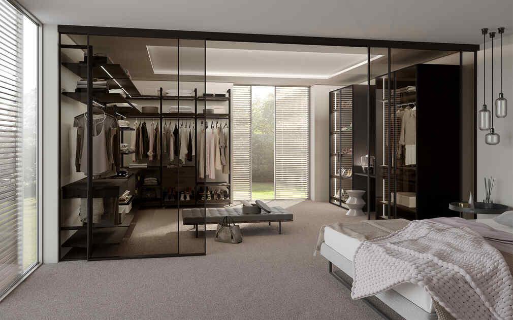 Ein Ankleidezimmer hinter einem Raumtrenner, integriert ins Schlafzimmer mit Regalen und einer Sitzmöglichkeit in der Mitte