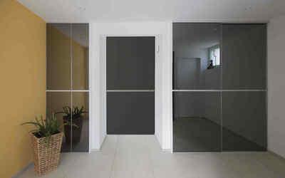 Edel gestalteter Einbauschrank mit grau-verspiegelten Schiebetüren als Fronten und passender Durchgangstüre dazwischen