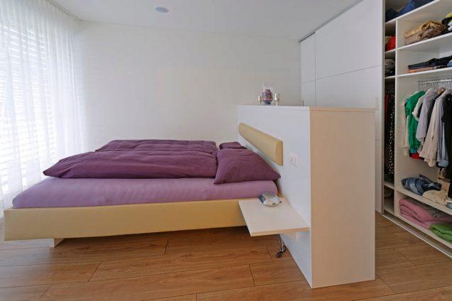 Ein violettes Bett mit einem Raumtrenner oder einer Mittelinsel als Kopfende welche nur brusthoch ist. diese trennt das Schlafzimmer vom eigentlichen Ankleidezimmer. Dahinter liegt ein begehbarer Kleiderschrank welcher das Ankleidezimmer um seine Funktionen ergänzt.