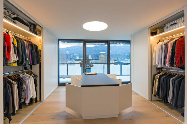 Ein Ankleidezimmer mit weißen Schiebetürschränken rechts und links und einer wundervollen Aussicht durch die frontseitig situierten Fenster. In der Mitte befindet sich eine Mittelinsel mit geöffneten Drehtüren. Die Schiebetürschränke sind innerhalb mit einem elektronischen Sensor beleuchtet.