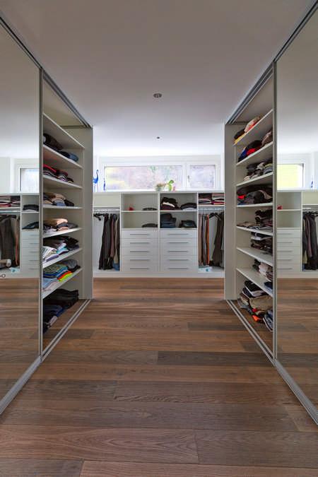 Dieses Gang-Ankleidezimmer ist rechts und links mit Schiebetürschränken ausgestattet, deren Schiebetüren verspiegelt sind. am Gangende befinden sich Regale mit Schubladen und Kleiderstangen. Die Schiebetürschränke rechts und links sind geöffnet und darin befinden sich riesige Regale.