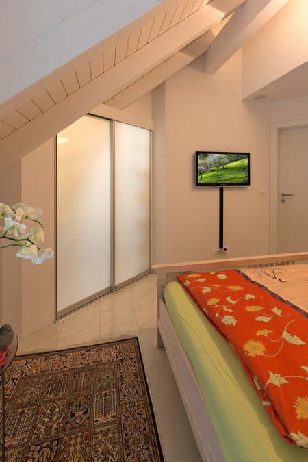 Ein geschlossener Durchgang welcher in einen tiefen Raum in der Dachschräge führt. Die Abtrennung zwischen diesem Raum und dem Schlafzimmer besteht aus Acrylglasschiebetüren, welche teilweise lichtdurchlässig sind und in diesem Fall von hinten beleuchtet werden. Weiters zeigt dieses Foto noch ein Bett und einen Fernseher.