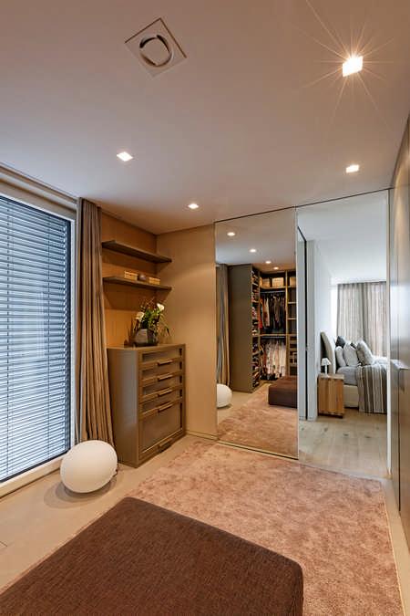 Der Ausgang des Ankleidezimmers mit einer Spiegelschiebetür und einem Beistellkasten mit Schubladen und ein paar Regalen