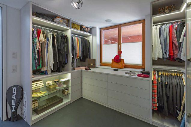 Ein besonderes Ankleidezimmer mit einer Vitrine links unten. Gleichzeitig ist ein Seitensystem verbaut welches mit Tablaren und Kleiderstangen kombiniert wurde. Auch zwei Schubladenkorpusse sind in diesem Ankleidezimmer verbaut. Darüber befindet sich ein Fenster ins Freie.