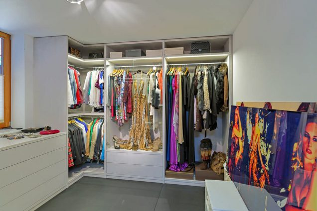 Ein Ankleidezimmer mit extrem viel Stauraum, welches sehr bunt mit Kleidern gespickt ist. Es ist ausgestattet mit einem Seitensystem inklusive mehreren Kleiderstangen und Tablaren. Auch Schubladen sind einige vorhanden.