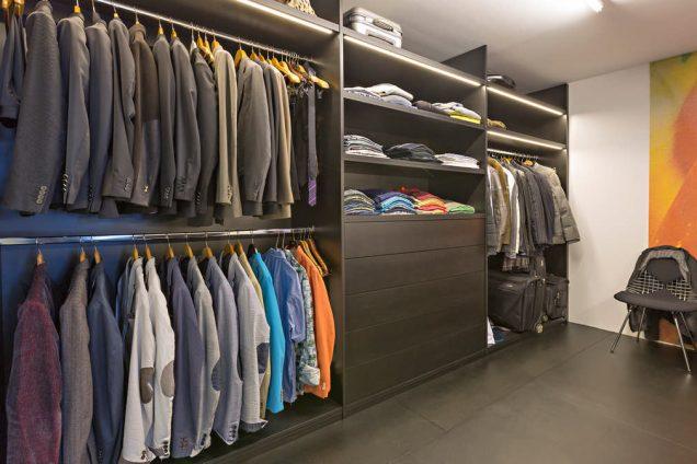 Hier werden dunkle Schubladen in einem Seitensystem gezeigt, welche Teil eines Ankleidezimmers sind. Diese sind mit Kleiderstangen und Unmengen Klamotten gefüllt. Alles ist raumhoch und bietet extrem viel Platz.