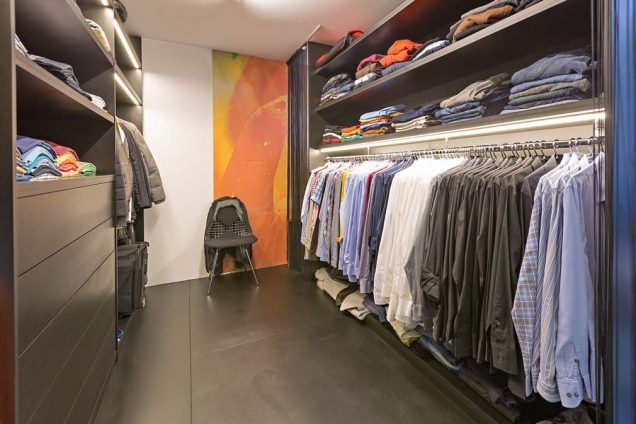 Ein Ankleidezimmer wie aus einem Kleidungsgeschäft. Ausgestattet mit allem was man braucht. Dunkle Regale kombiniert mit einer Kleiderstange. Im hinteren Bereich befindet sich eine Umkleidekabine. Links sind weitere Schubladen, Regale und Kleiderstangen und am ende des Ankleidezimmers befindet sich ein einladender Stuhl