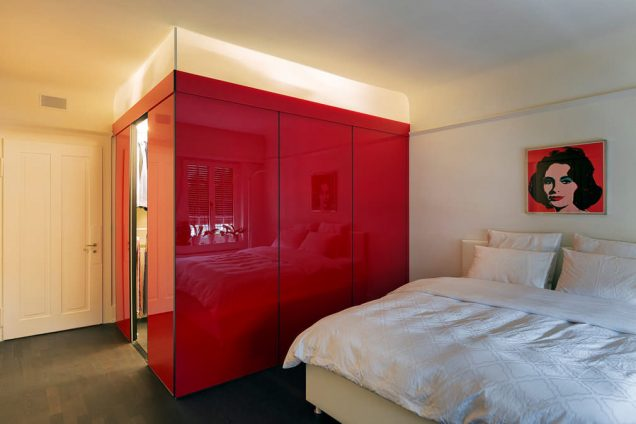 Ankleidezimmer in leuchtendem Rot mit Hintergrundbeleuchtung hinter Acrylgläsern am Kopfende