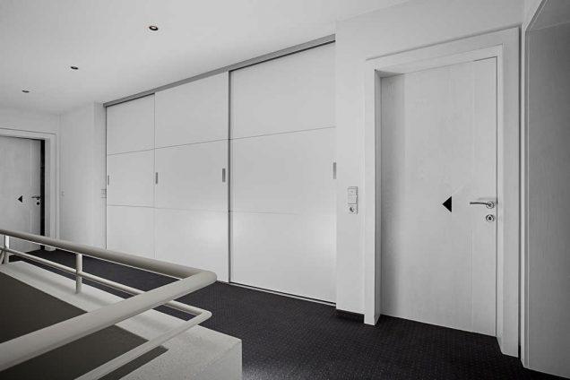 Der hier dargestellte Einbauschrank fügt sich perfekt in seine Umgebung ein. Er besteht aus weißen Hochglanzschiebetüren, welche in eine weiße Wandöffnung eingepasst worden sind. Die Schiebetüren sind besonders groß und breit. Der anthrazitfarbene Fliessenboden ist offensichtlich teil einer Gangfläche.