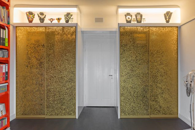 Der hier dargestellte Einbauschrank besteht aus geschlossenen goldenen Schiebetüren, welche richtig schimmern. Über den Schiebetüren befinden sich zwei Glasvitrinen, welche von innen beleuchtet sind und darin befinden sich mehrere Büsten mit den unterschiedlichsten Ketten. In der Mitte ist eine weiße Tür, die augenscheinlich in einen anderen Raum führt.