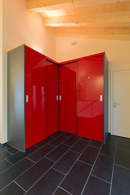 Ein Eckschrank oder auch begehbarer Kleiderschrank mit leuchtend roten Schiebetüren, welche im Eck aufeinander zulaufen. Sogar die Ecke ist hier nutzbar