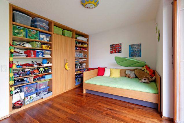 Dieser Einbauschrank besteht hauptsächlich aus offenen Regalen, welche die gesamte Wand ohne Luftraum einnehmen. Die Regale sind gut gefüllt mit allerlei Spielsachen und Boxen. In der Mitte befindet sich ein Drehtürenschrank mit einem gelben Mondanhänger am Griff. Rechts ist ein Kinderbett mit grünem Bettbezug und bunten Kissen.