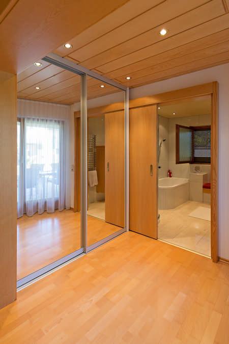 Dieser Einbauschrank besteht aus raumhohen verspiegelten Schiebetüren und befindet sich vor dem Bad. Die Schiebetüren sind geschlossen und man kann das gegenüberliegende Fenster sehen.