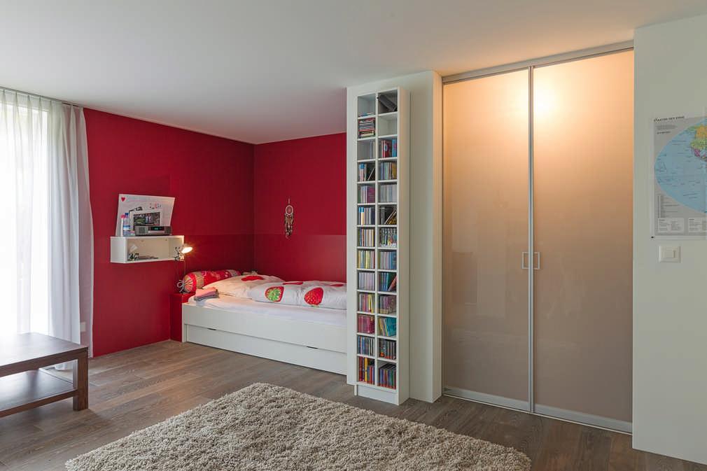 Ein begehbarer Kleiderschrank im Schlafzimmer mit Acrylglasschiebetüren als Abschluss