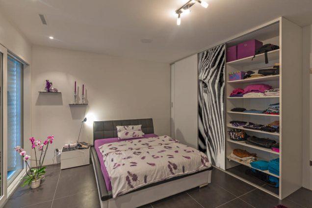 Dargestellt ist ein Schlafzimmer mit einem Bett als Sonderanfertigung in violett- und Anthrazittönen. Rechts davon ist ein Einbauschrank mit einer weißen Schiebetür und einer, auf der ein Zebrakopf abgebildet ist. Das ganze Ambiente wirkt sehr modern und aufregend. In dem Einbauschrank ist ein Regal abgebildet, welches mit allen möglichen Alltagsgegenständen gefüllt ist.