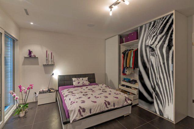 Dargestellt ist ein Schlafzimmer mit einem Bett als Sonderanfertigung in violett- und Anthrazittönen. Rechts davon ist ein Einbauschrank mit einer weißen Schiebetür und einer, auf der ein Zebrakopf abgebildet ist. Das ganze Ambiente wirkt sehr modern und aufregend. In dem Einbauschrank befinden sich mehrere Schubladen und Kleiderstangen gefüllt mit allen möglichen Kleidungsstücken. Im oberen Bereich ist noch ein zusätzliches Regal, das noch mehr Stauraum bietet.