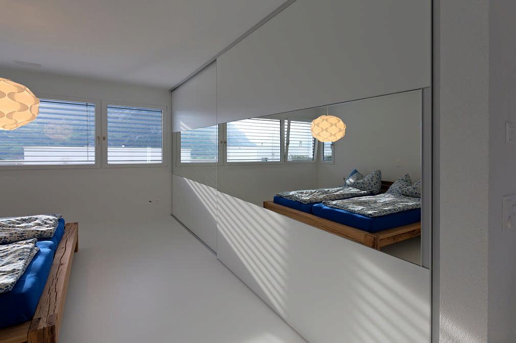 Wir befinden uns im Schlafzimmer. Das Bett ist teilweise noch dargestellt. Hier befindet sich ein großer Einbauschrank mit geschlossenen Schiebetüren. Die Schiebetüren des Einbauschrankes bestehen oben und unten aus einer Hochglanzoberfläche und in der Mitte befindet sich ein Spiegel über die gesamte Breite, in dem die Spiegelung des Schlafzimmers und des Bettes ersichtlich ist.