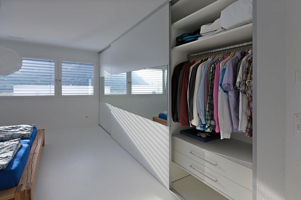 Ein teilweise geöffneter in schlichtem Weiß gehaltener Einbauschrank. In der Mitte befindet sich ein Spiegelband, welches über alle Schiebetüren der länge nach zieht. In dem Schrank befinden sich Schubladen, Kleiderhaken und Regale für die Kleider im Sclafzimmer.