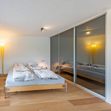 Ein Designerbett mit einem Einbauschrank neben sich. Der Einbauschrank ist komplett geschlossen und in seinen Schiebetüren spiegelt sich das Licht einer Lampe aus dem Schlafzimmer.