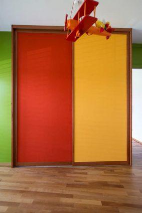 Der hier dargestellte Einbauschrank ist geschlossen. Die Schiebetüren sind gelb und rot und im Hintergrund befindet sich eine grüne Wand