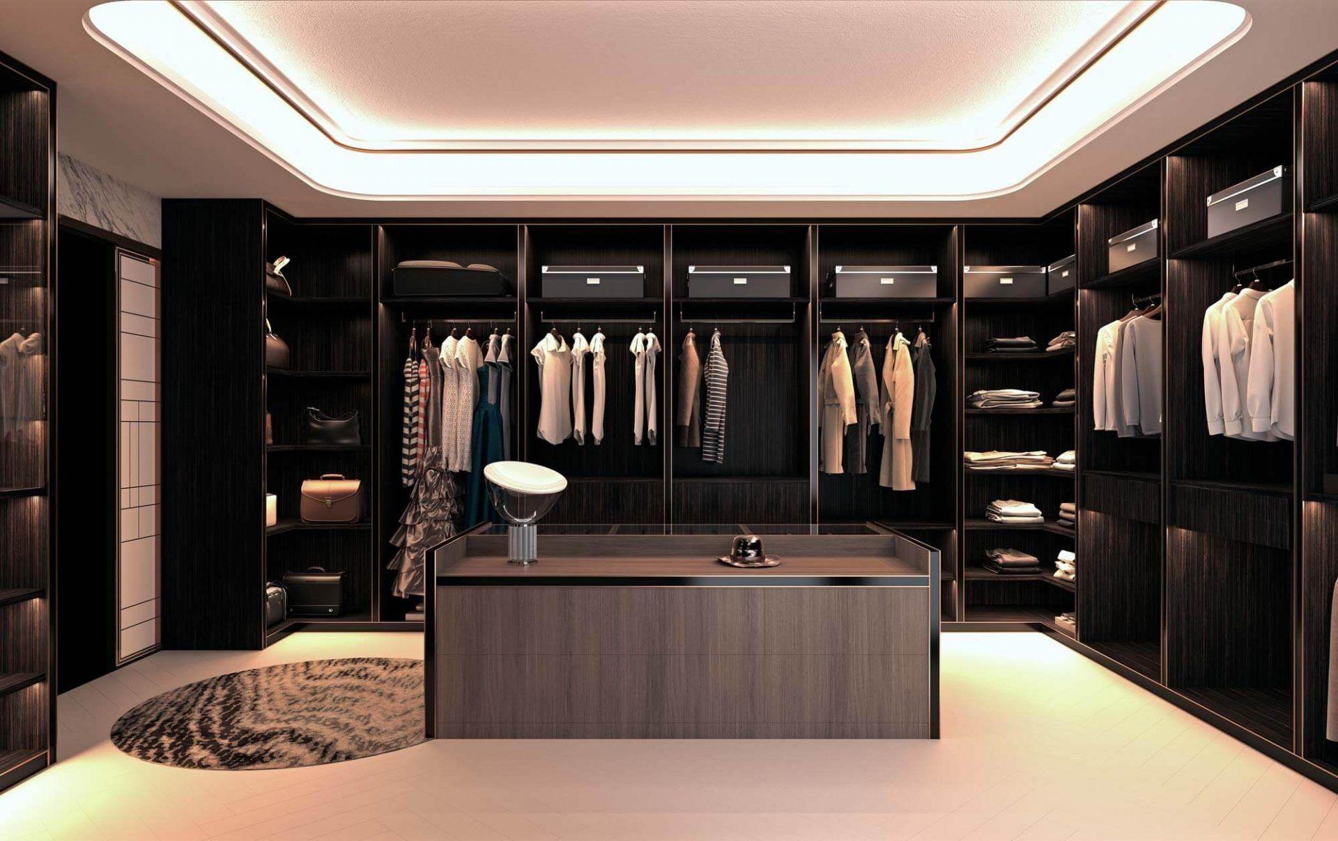 Ankleidezimmer mit Mittelinsel und versteckter Beleuchtung in bescher Tönung mit einem Seitensystem aus Regalen mit vielen Kleiderstangen